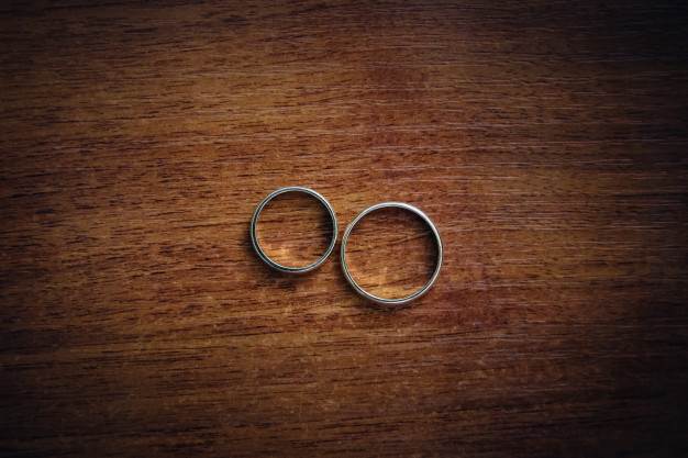 silver-wedding-rings-lie-on-the-wooden-table_8353-689